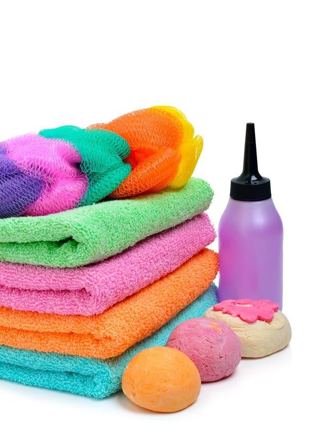 Las toallas del balneario, las bombas del baño y el champú apilados coloridos embotellan isola fotografía de archivo