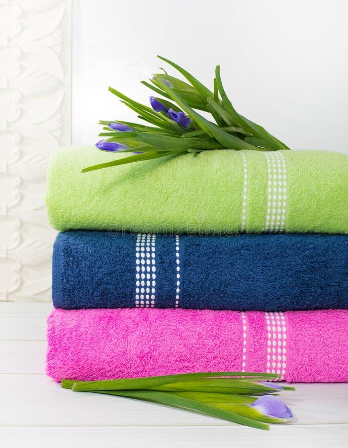 Toallas en la pila contra el contexto blured, pila de toallas verdes, azules, yelloy y rosadas con las flores imágenes de archivo libres de regalías