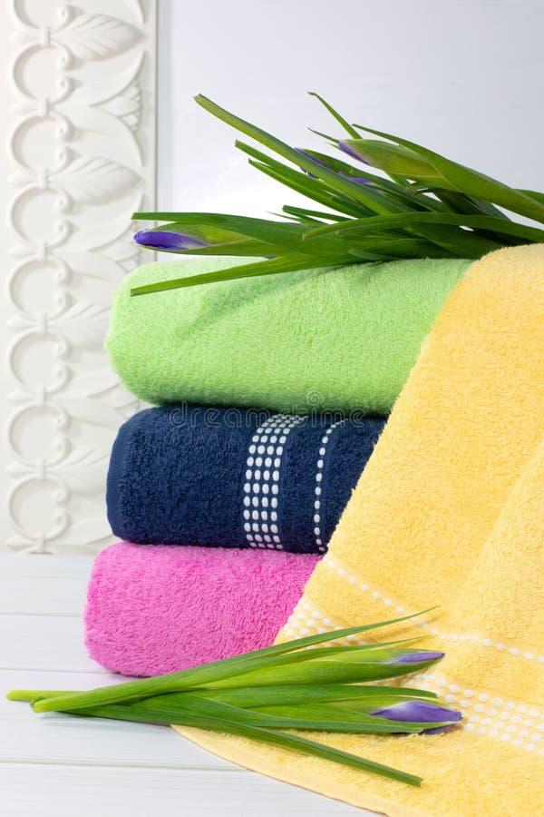 Toallas en la pila contra el contexto blured, pila de toallas verdes, azules, yelloy y rosadas con las flores fotos de archivo