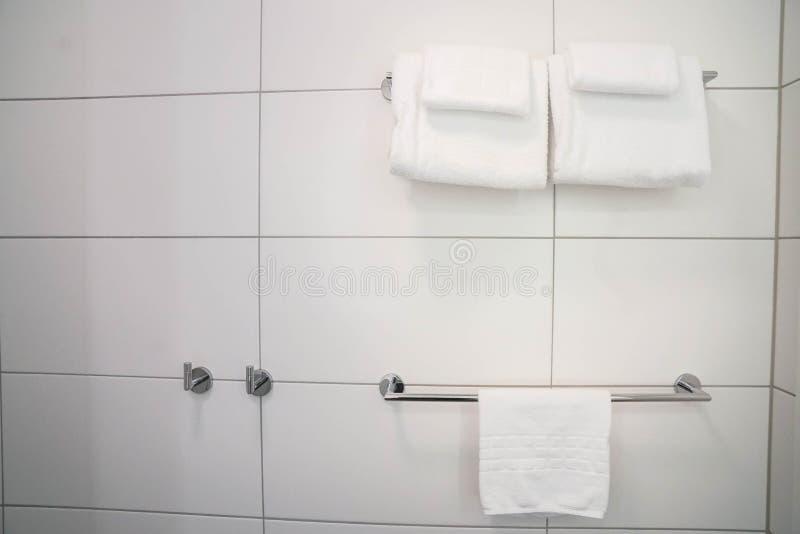 Toallas suaves blancas del algodón en el carril del cuarto de baño para la ducha en hotel de lujo imagen de archivo