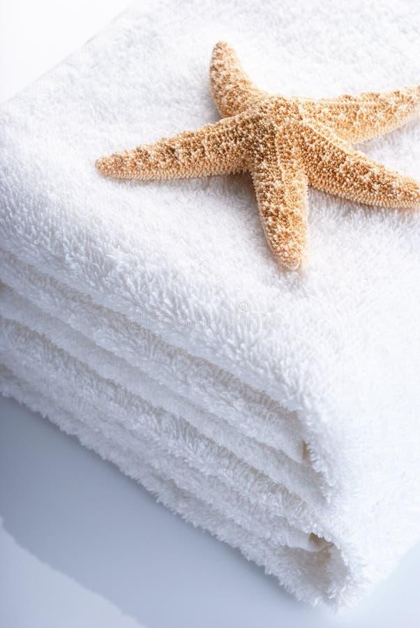 Toallas y estrellas de mar blancas imagenes de archivo