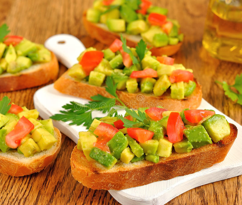 Toast with avocado. On a brown table stock images