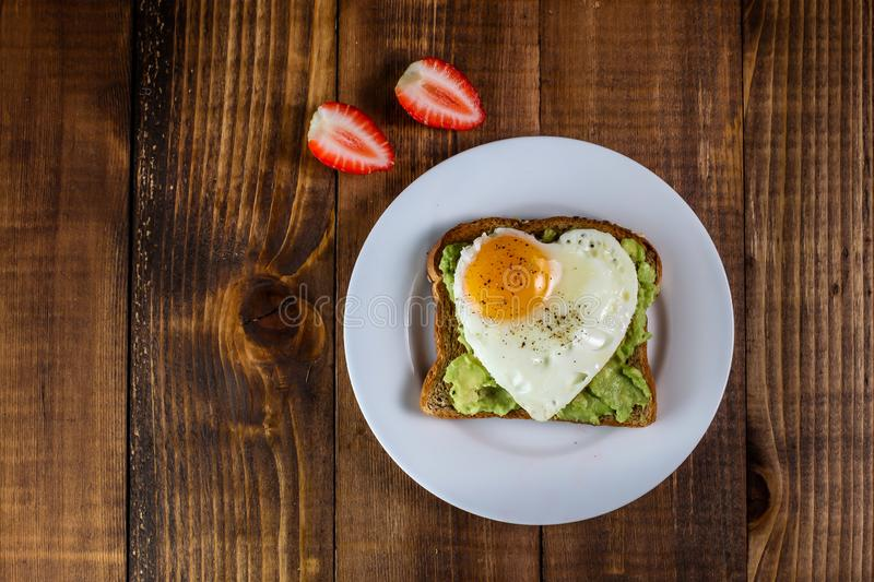 Toast with avocado and egg in heart shape and strawberries stock image
