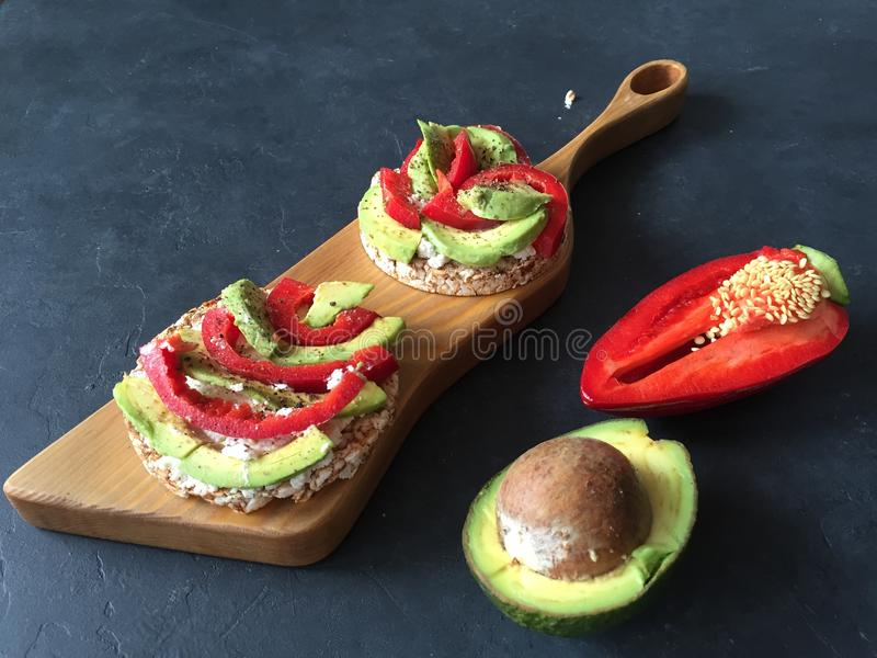 Toast with avocado, pepper and cheese on colored concrete background. stock photos