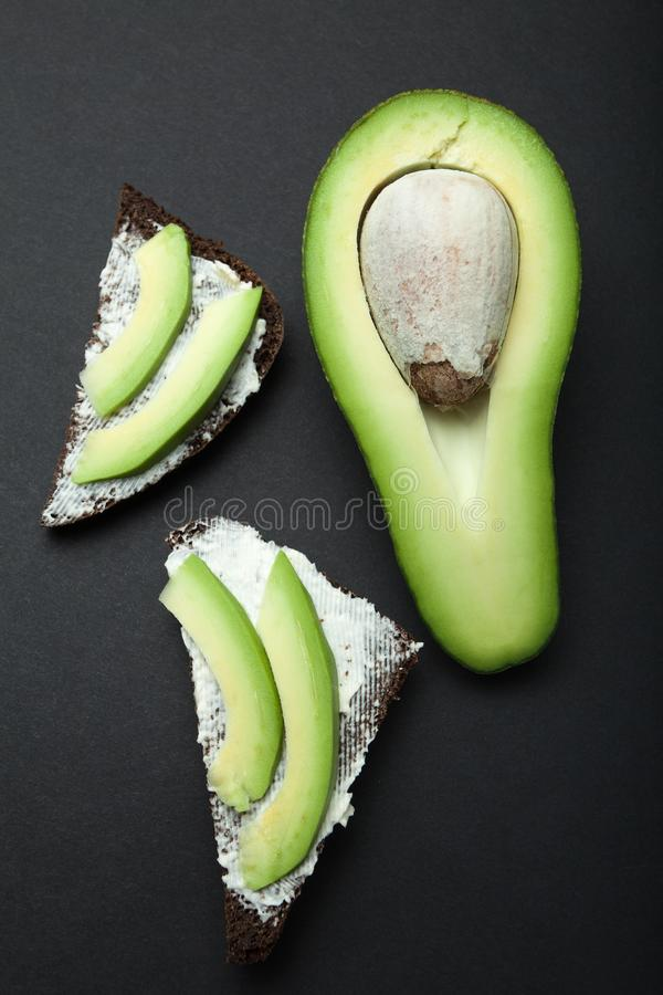 Toast of black bread and pieces of avocado on a black background, vertically royalty free stock photography