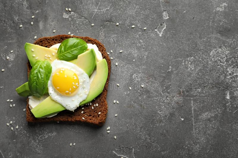 Toast bread with cream cheese, avocado and fried egg. On dark background stock photography