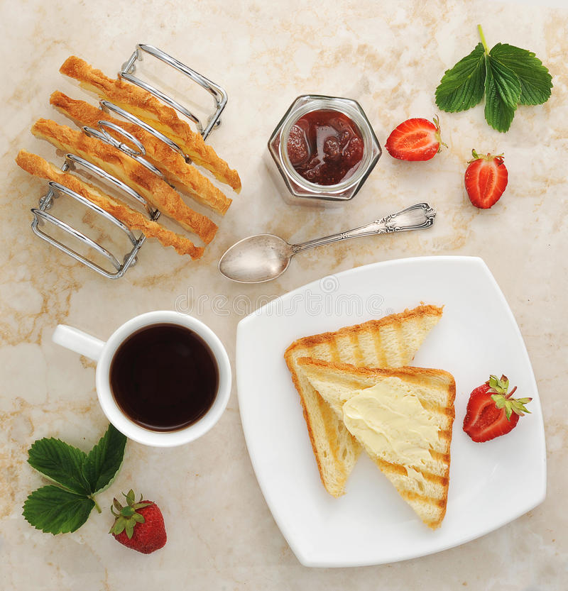 Toast with butter and jam on plate and cup of tea royalty free stock photos