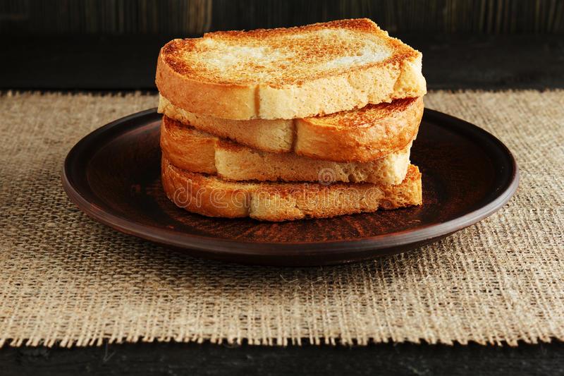 Toast in a clay plate. On a wooden table with burlap royalty free stock photos