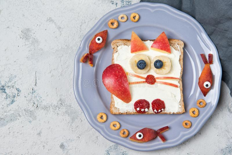 Toast with cream cheese spread in a shape of cat, food for kids idea, top view stock images