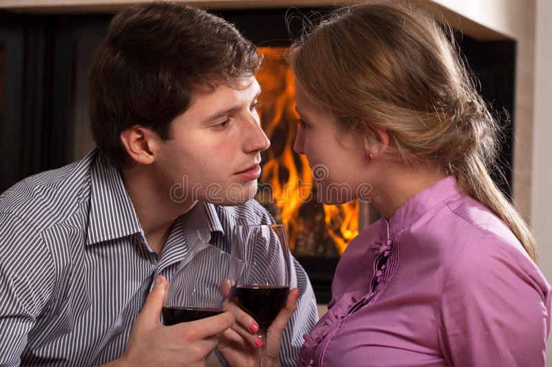 Toast by fireplace. A couple proposing a toast by a fireplace royalty free stock photos