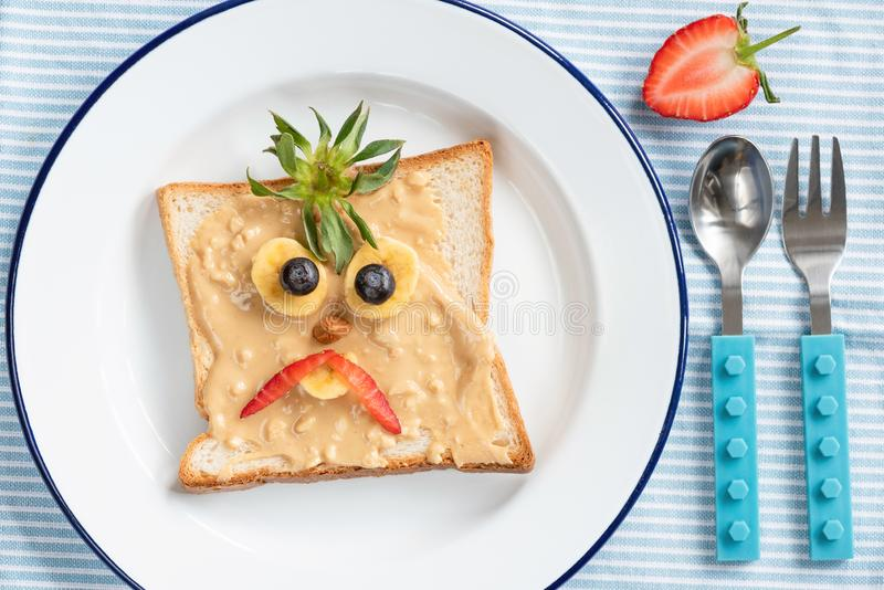 Toast with funny face for kids. Angry Bird face on peanut butter toast, kids breakfast royalty free stock photo