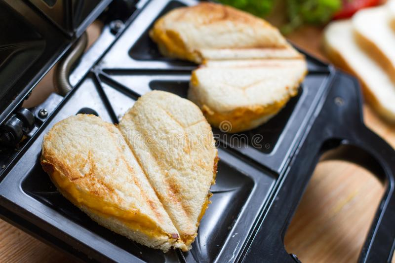 Toast heart shape with toaster sandwich maker love valentines breakfast concept. Closeup royalty free stock photo