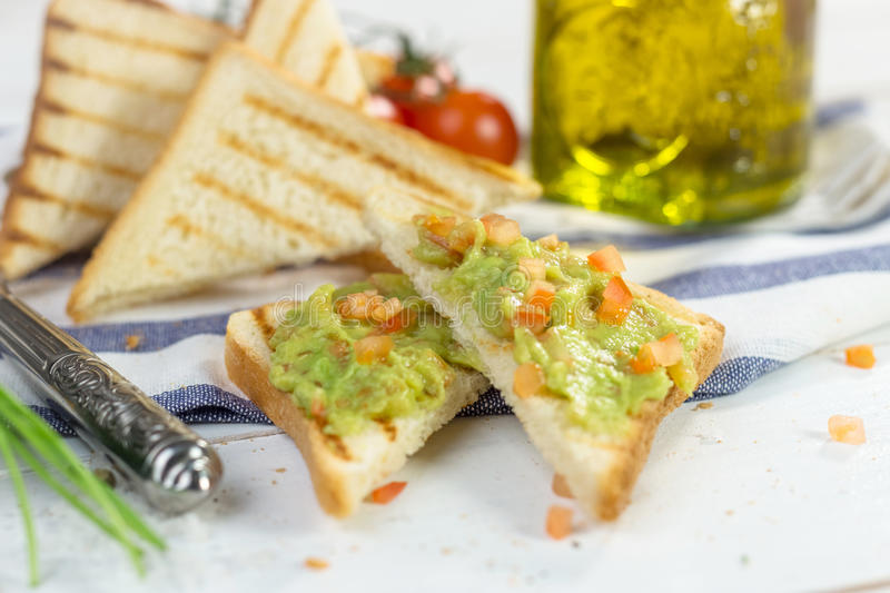Toast with mashed avocado, olive oil and tomato stock photography