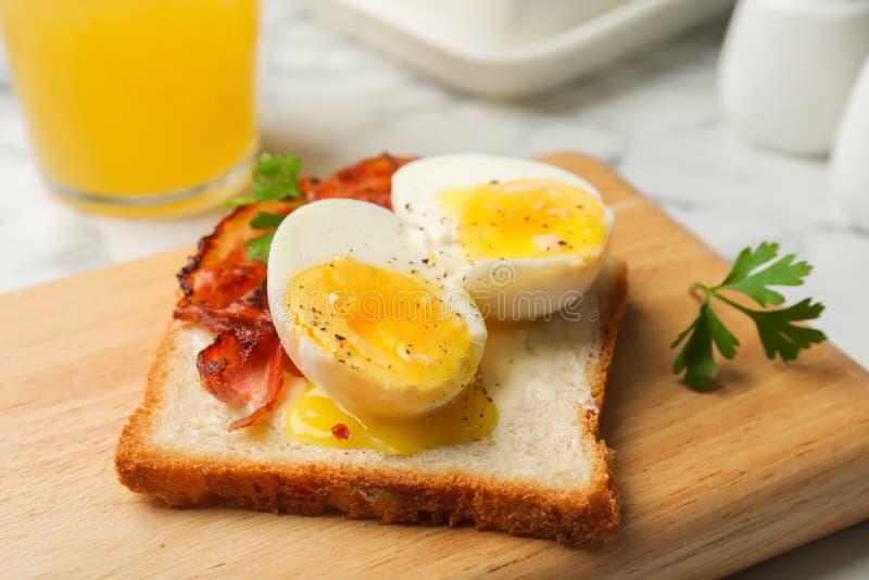 Toast mit weichem gekochtem Ei und Speck auf hölzernem Brett stockfotos