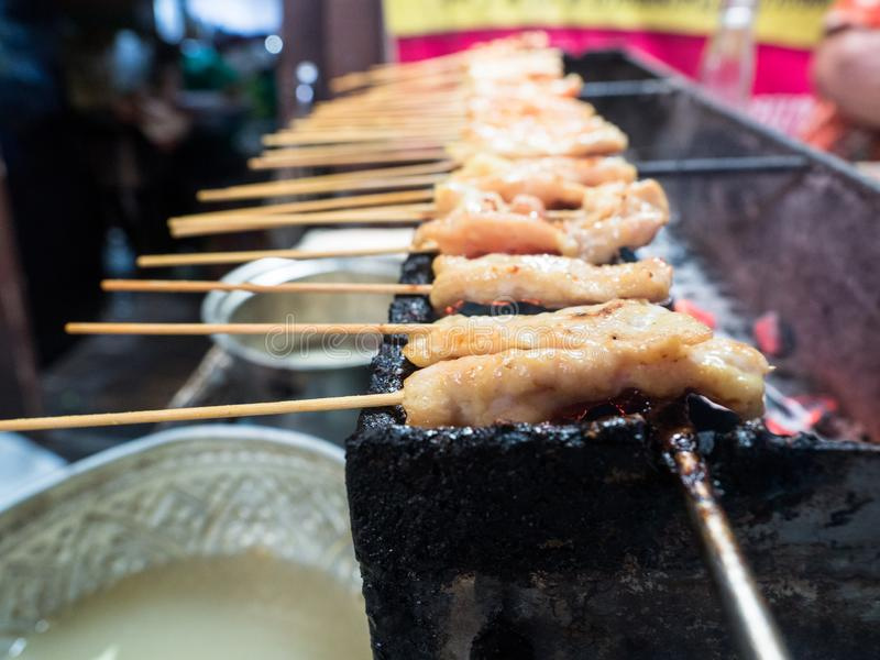 Toast pork with bamboo stick. Insert on iron charcoal stove for sale stock images