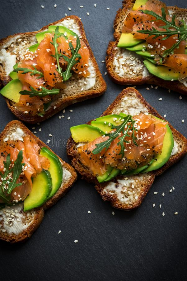 Toast sandwich with butter, avocado and salmon, decorated with arugula and sesame seeds, on a black stone board stock image