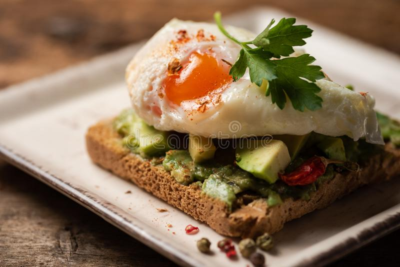 Toast sandwich with fried egg. Fresh toast sandwich with fried egg and avocado, guacamole, toasted, sunny, side, up, close, served, plate, food, snack, bread royalty free stock photos
