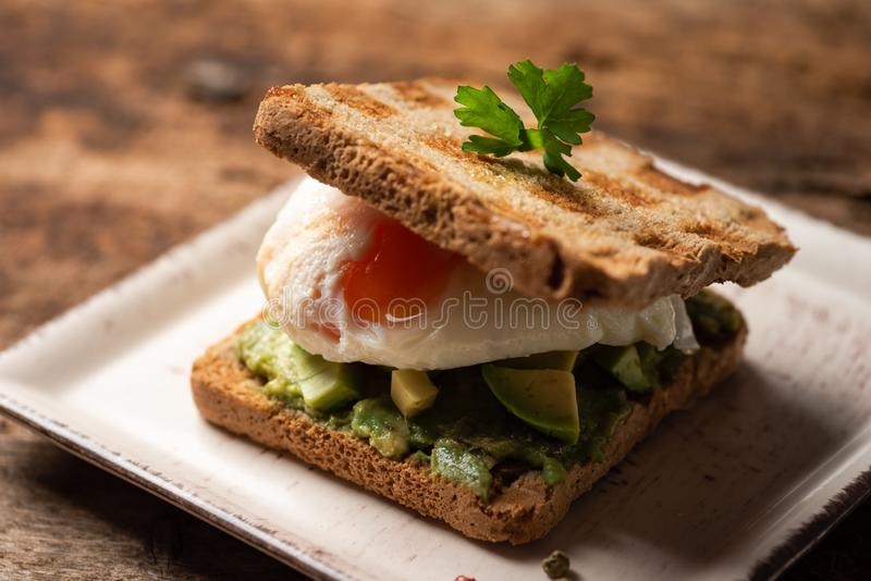 Toast sandwich with fried egg. Fresh toast sandwich with fried egg and avocado, guacamole, toasted, sunny, side, up, close, served, plate, food, snack, bread royalty free stock photography