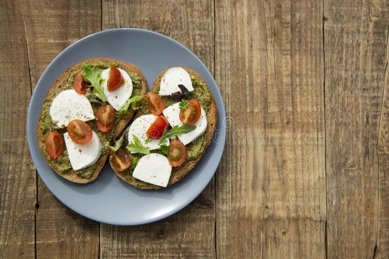 Toast sandwich mozzarella cheese, cherry tomatoes and pesto bruschetta, toast on wooden background. Healthy breakfast, snack. Copy stock images
