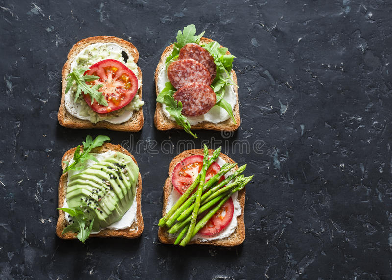 Toast sandwiches with avocado, salami, asparagus, tomatoes and soft cheese on dark background, top view. Tasty breakfast, snack or royalty free stock photography