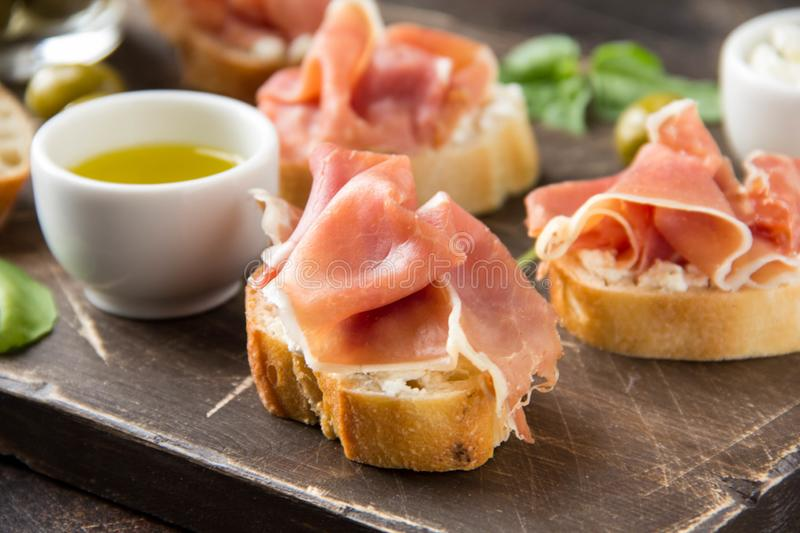 Toast with serrano ham (jamon, prosciutto crudo, hamon), traditional Italian antipasti. Delicious snack with bread, cream cheese, royalty free stock photos