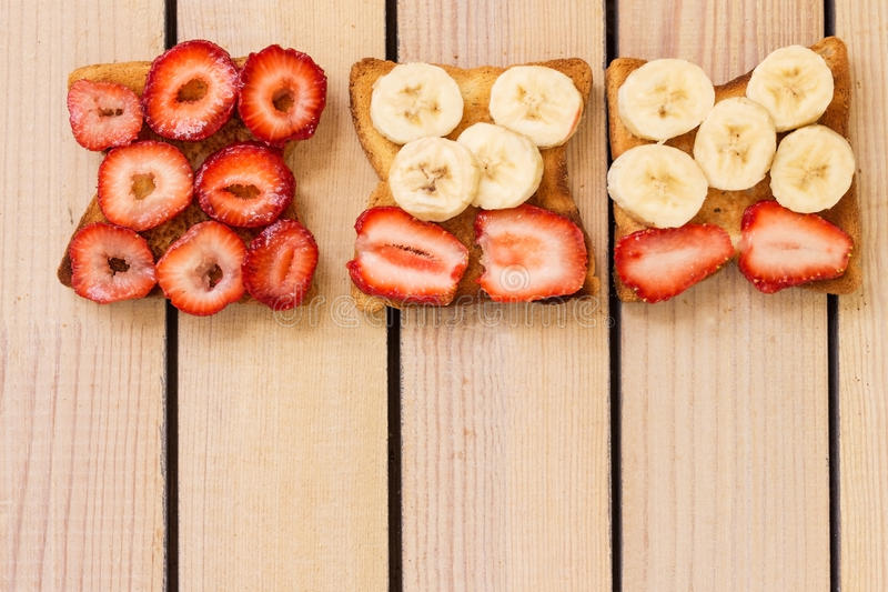 Toast with strawberries and bananas on a wooden background. Fresh toast with strawberries and bananas on a wooden background stock photos