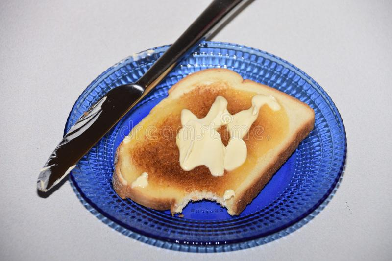 Toast So Tasty I couldn`t resist taking a bite!. Toast, Bread, Butter, Knife, Pretty Blue Glass Plate. Comfort Food for Many, a Staple in Britain, Toast isnt royalty free stock photos