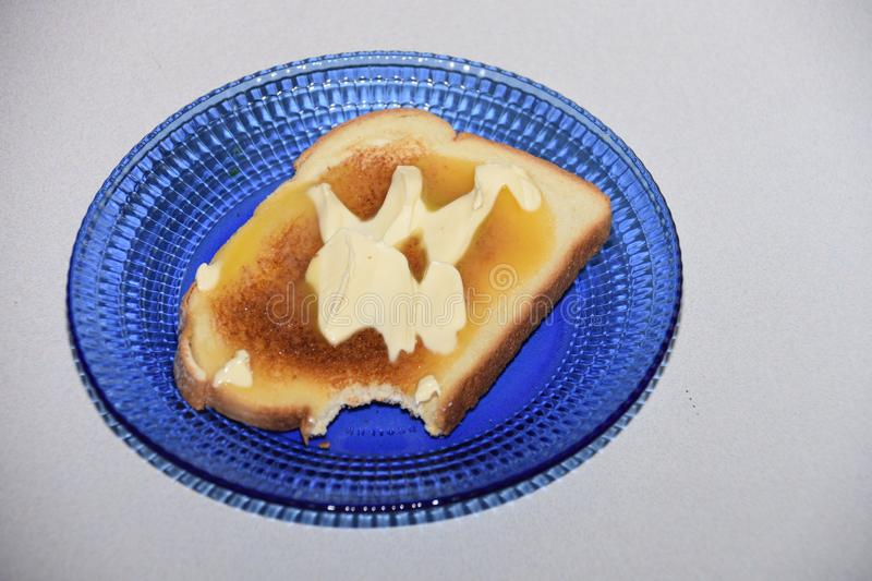 Toast So Tasty I couldn`t resist taking a bite Part 2. Toast So Tasty I couldn`t resist taking a bite! Toast, Bread, Butter, Knife, Pretty Blue Glass Plate royalty free stock images