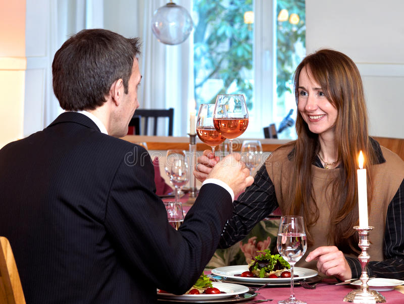 A toast to the future. A romantic middle-aged couple enjoying a candlelit dinner raise their wine glasses in a toast to the future royalty free stock photo