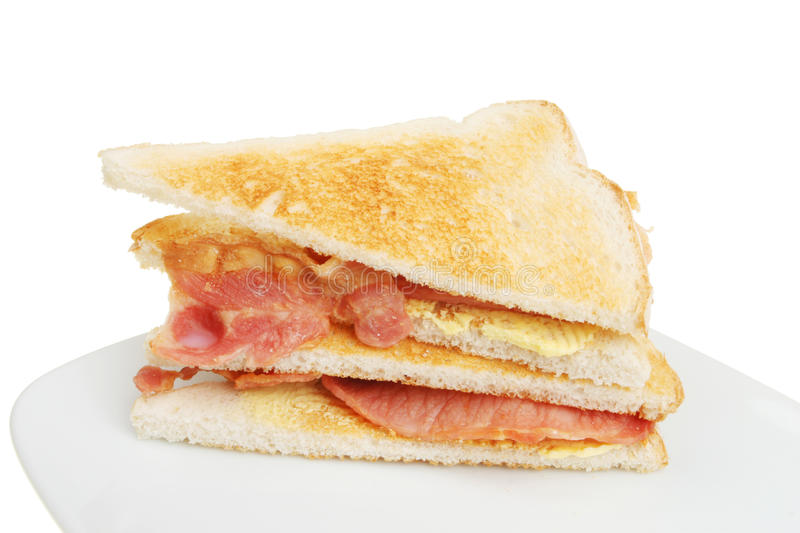 Toasted bacon sandwich. On a plate against a white background stock image