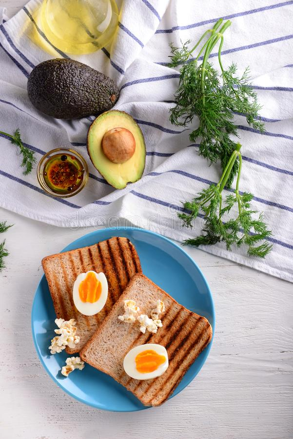 Toasted bread with cut boiled egg on plate stock images