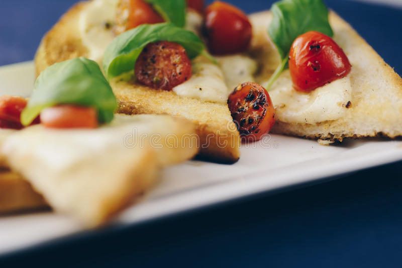 Toasted bread with mozzarella, cherry tomatoes and basil stock photography