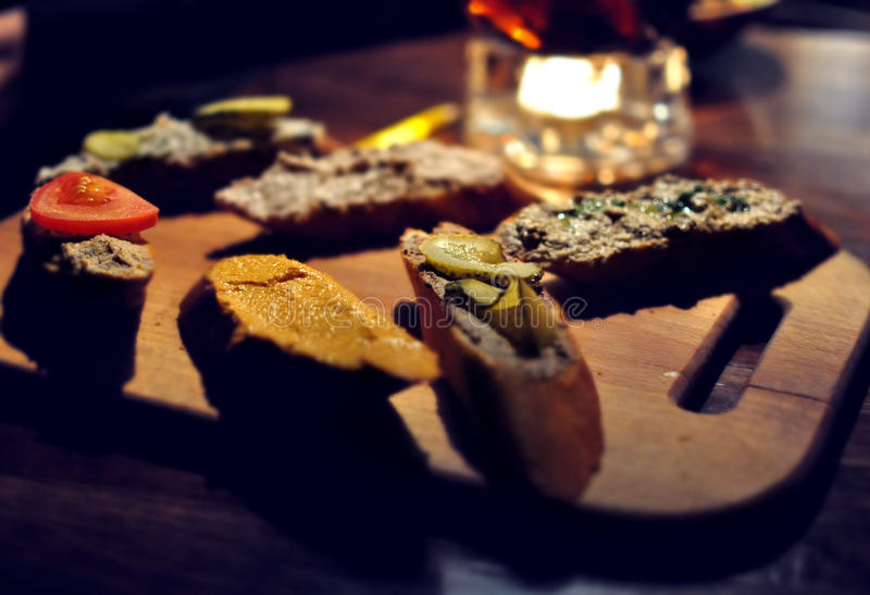 Toasted bread with pate, salmon and vegetables on wooden cutting board in a restaurant. Six different sandwiches, variety of royalty free stock image