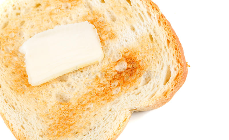 Toasted whole grain bread with a pat of butter. Isolated on white background royalty free stock photography