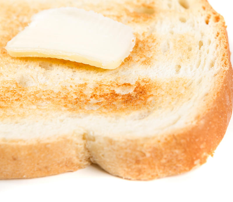 Toasted whole grain bread with a pat of butter. Isolated on white background royalty free stock photo