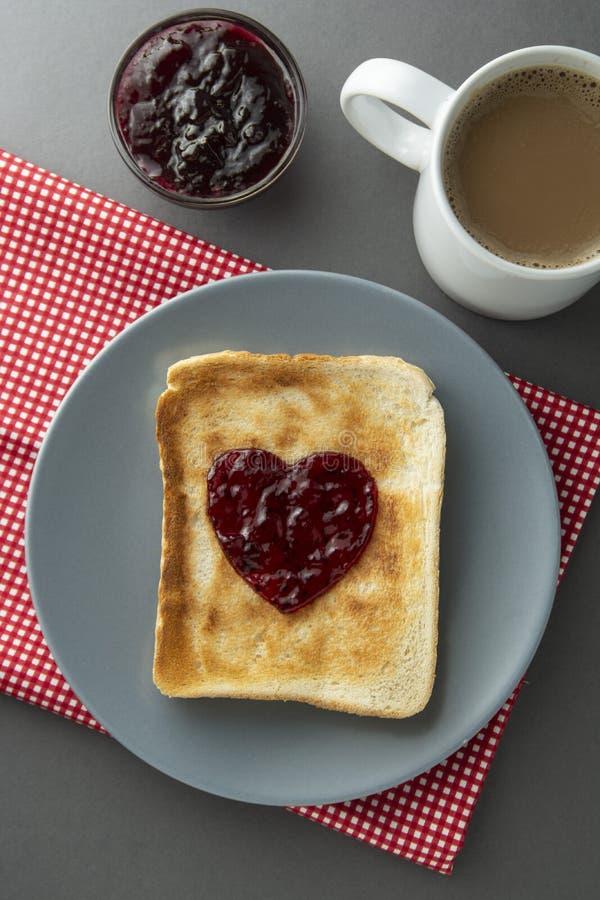 Toasten Sie Brot mit Stau in Form von Herzen und von Tasse Tee Gesundes Frühstück mit Toast- und Fruchtstau lizenzfreies stockbild