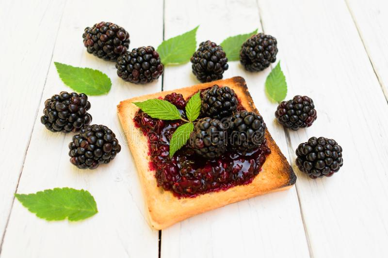 Toaster with blackberry jam. Decorated with fresh berries and blackberry leaves. stock images