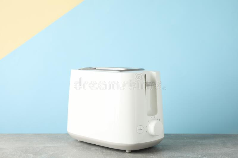 Toaster on grey table against color background. Space for text stock images