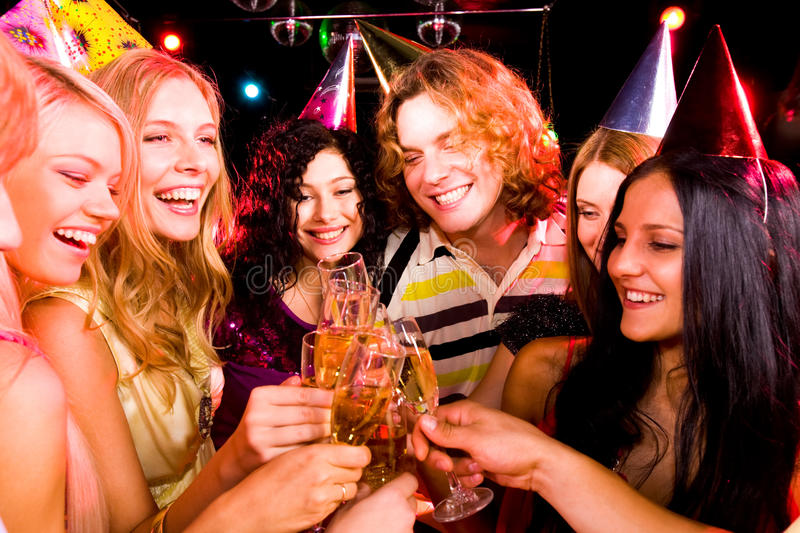 Toasting. Portrait of boozing people in smart clothing toasting at birthday party stock image