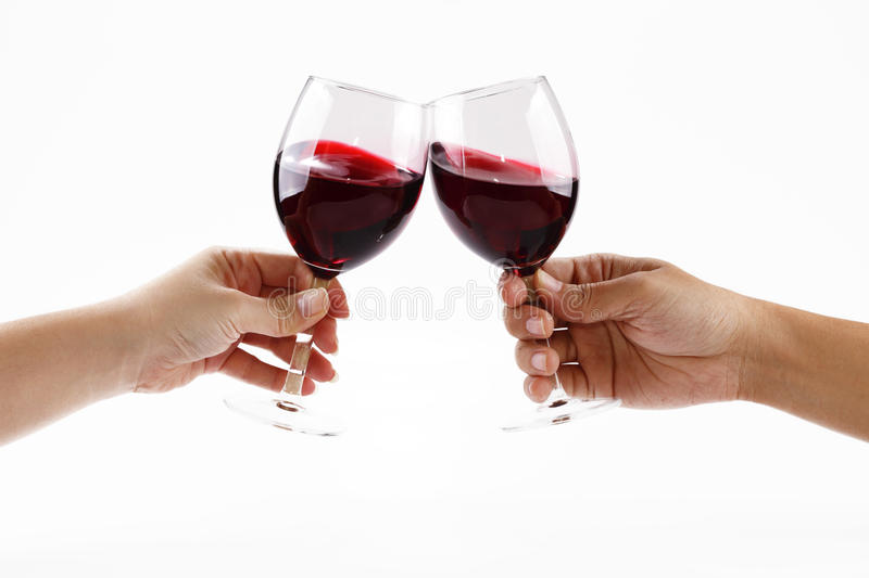 Toasting. Two people toasting with wine glasses filled with red wine royalty free stock images