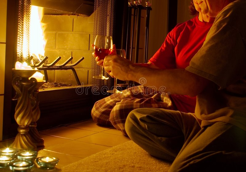 Toasting. Man and woman toasting each other with a glass of wine in front of a fireplace stock photo