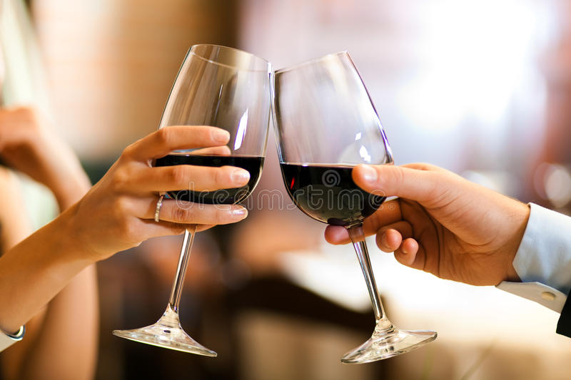 Toasting. Couple toasting wineglasses in a luxury restaurant royalty free stock photo