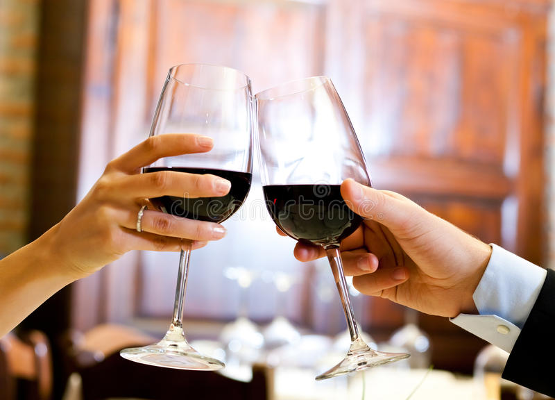 Toasting. Couple toasting wineglasses in a luxury restaurant royalty free stock photography