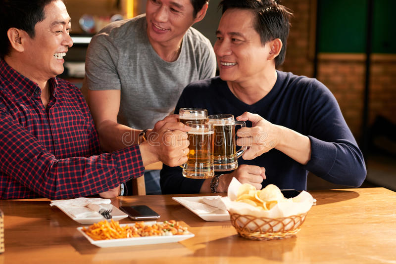 Toasting friends. Laughing male friends toasting with beer mugs royalty free stock images