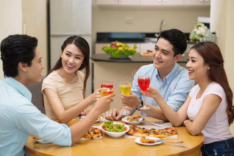 Toasting friends. Young happy friends toasting at the dinner table royalty free stock image