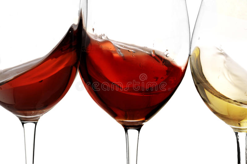 Toasting gesture red and white wine with splash, cheers close up with wine isolated. Red and white and rosé wine. Isolated with white background royalty free stock image