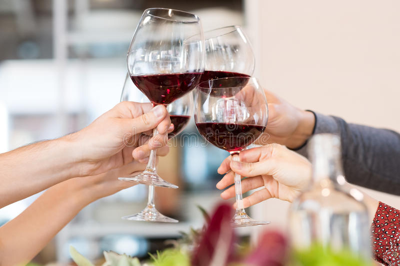 Toasting glasses. Close up of glasses raising a toast at lunch. Closeup of friends toasting glasses of red wine in a party. Group of friends a toast to the royalty free stock images