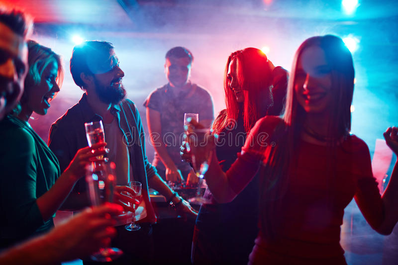Toasting at party. Happy friends toasting at night party stock photography
