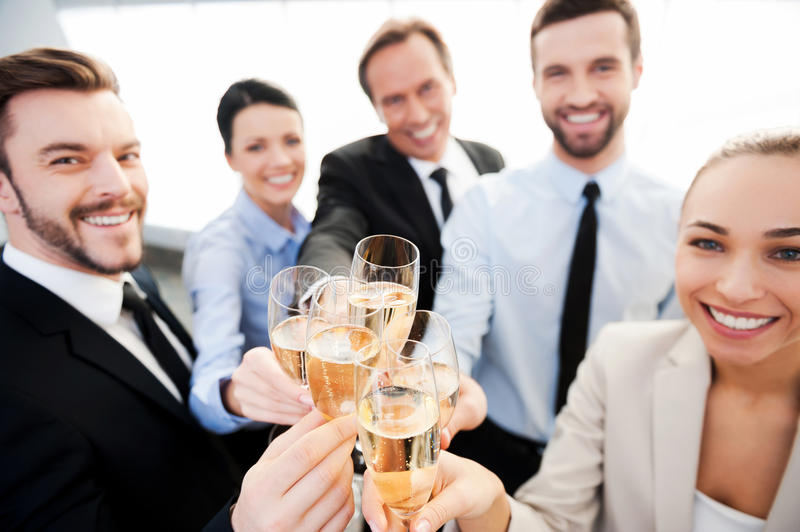 Toasting to success. Group of business people toasting with champagne and smiling while standing close to each royalty free stock images