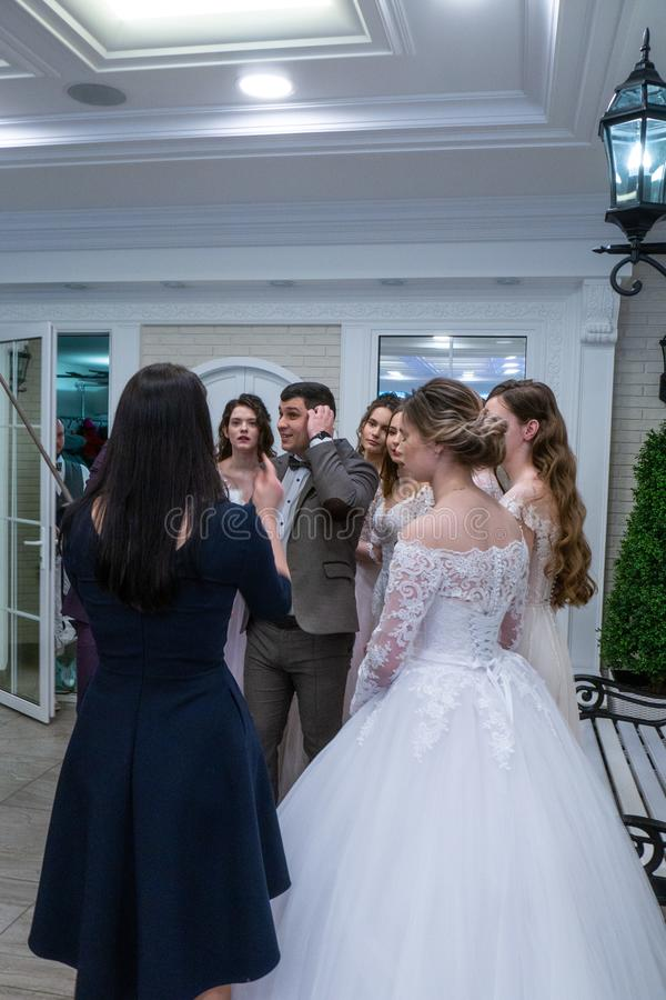 A toastmaster among bride models shows soomething. At the exhibition Wedding hassle 2019 took place in Kirov, Russia stock photo